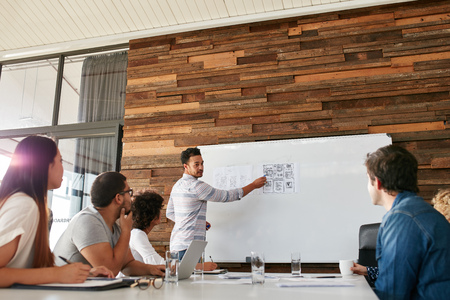Foto de Portrait of young businessman giving presentation to colleagues. Young man showing new app design layout on white board to coworkers during business presentation. - Imagen libre de derechos