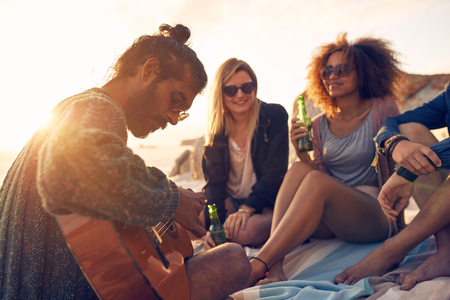 Foto de Hipster playing guitar for friends at the beach. Group of young people drinking beer and listening to music. - Imagen libre de derechos
