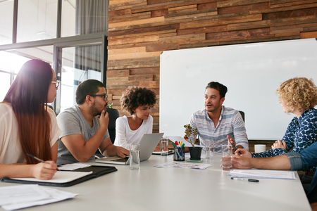 Foto de Shot of a group of young business professionals having a meeting in boardroom. Office workers discussing new business plan together in a conference room. - Imagen libre de derechos