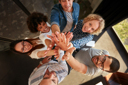Foto de Top view of successful team of professionals high fiving and looking at camera smiling. Men and women making a pile of hands in office. - Imagen libre de derechos