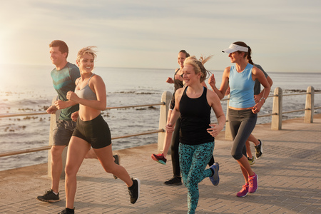 Portrait of young people running by the sea in morning, Healthy young men and women doing running workout.