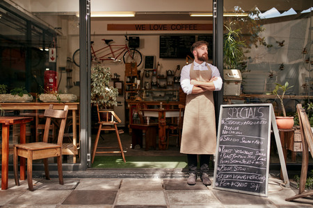 Foto de Portrait of a young man standing in front of his coffee shop. Young man with beard wearing an apron  standing with her arms crossed and looking away. - Imagen libre de derechos