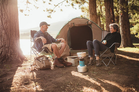 Foto de Portrait of happy senior couple sitting in chairs by tent at campsite. Mature man and woman relaxing and talking near a lake on a sunny day. - Imagen libre de derechos