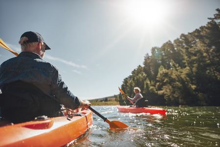 Photo pour Image of senior couple canoeing in the lake on a sunny day. Kayakers in the lake paddling. - image libre de droit
