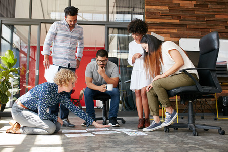 Foto de Creative people looking at project plan laid out on floor. Mixed race business associates discussing new project plan in modern office. - Imagen libre de derechos