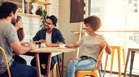 Portrait of a young group of friends meeting in a cafe. Young men and women sitting at cafe table and talking.