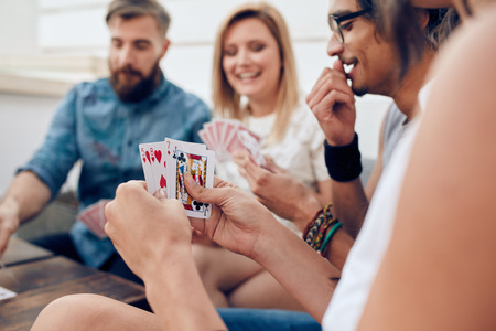 Foto de Group of friends sitting together playing cards. Focus on playing cards in hands of a woman during a party. - Imagen libre de derechos
