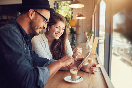 Photo for Happy couple in a coffee shop surfing internet on digital tablet. Young man and woman in a restaurant looking at touch screen computer. - Royalty Free Image
