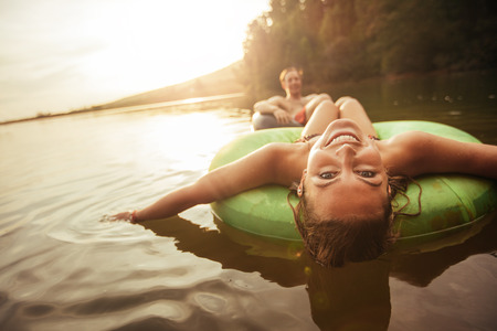 Photo pour Portrait of happy young woman floating in an innertube with her boyfriend in background at the lake. Young couple in lake on inflatable rings. - image libre de droit