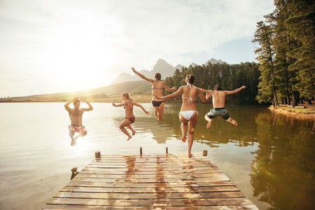 Portrait of young friends jumping into the water from a jetty. Young people having fun at the lake on a summer day.
