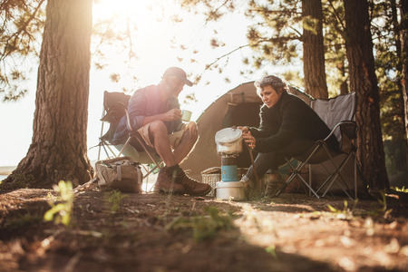 Senior couple cooking and making food outdoors on a camping trip. Mature man and woman sitting outside the tent on a summer day at campsite.