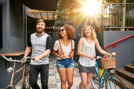 Three young adults walking together having fun. Young people with bikes walking outdoors in city.