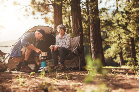 Happy campers outdoors in the wilderness and making coffee on a stove. Senior couple on a camping holiday.