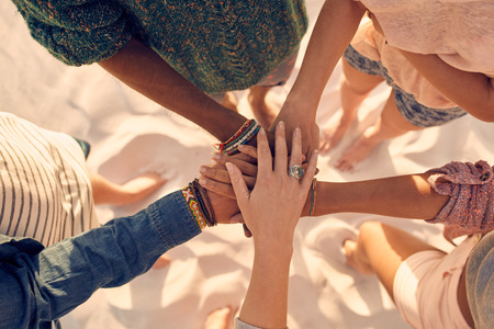 Photo for Group of young men and women showing unity. Group of young friends putting their hands together at the beach. - Royalty Free Image