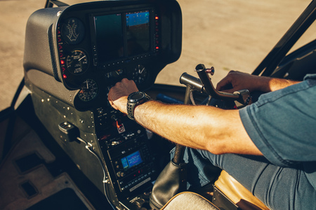 Close up shot of pilot checking the gauges on the instrument panel dashboard of  a helicopter. Pilot's hand on an helicopter instrument panel.