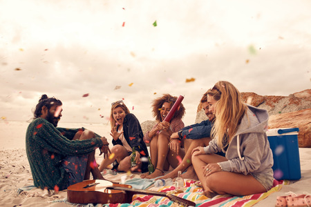 Photo pour Happy friends partying on the beach with drinks and confetti. Happy young people having fun at beach party, celebrating with confetti. - image libre de droit