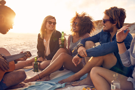 Photo pour Portrait of group of young friends having a party on the beach in evening. Men and women drinking beers and listening to friend playing guitar. - image libre de droit