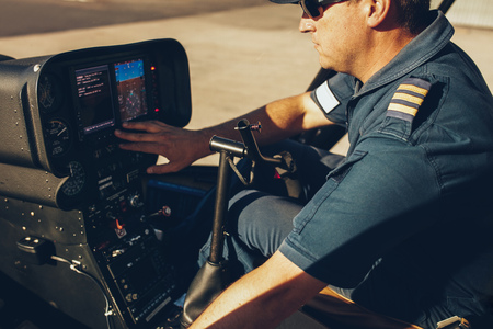 Close up shot of helicopter pilot checking the gauges on the instrument panel dashboard.