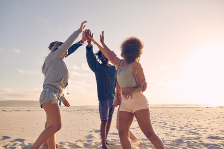Group of happy friends high fiving on the beach and having fun during summer. Mixed race people celebrating success.