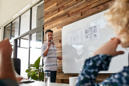 Foto de Young man discussing new mobile application design on white board with colleagues during a meeting. Business presentation in boardroom. - Imagen libre de derechos
