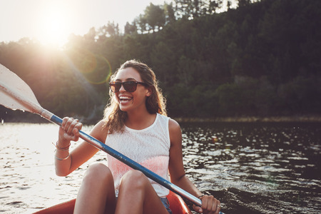 Foto de Smiling young woman kayaking on a lake. Happy young woman canoeing in a lake on a summer day. - Imagen libre de derechos