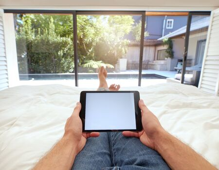 POV shot of man using digital tablet while lying on bed. Human hand holding digital tablet with blank screen.