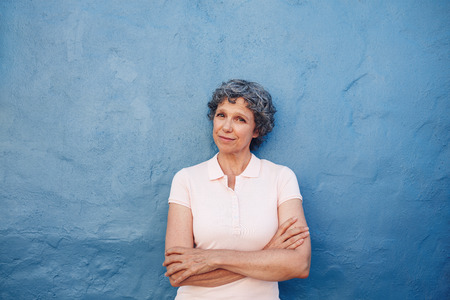 Portrait of beautiful senior woman standing with her arms crossed against blue wall. Happy mature female looking at camera.