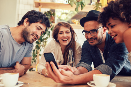 Photo pour Group of young people sitting in a cafe and looking at the photos on smart phone. Young men and women meeting at cafe table and using cell phone - image libre de droit