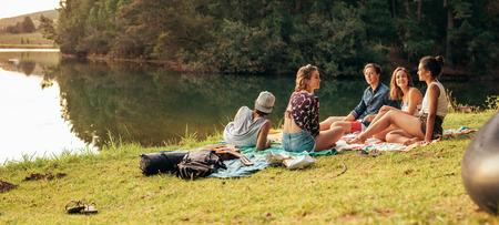 Photo pour Young friends having picnic near a lake. Young friends enjoying a day at the lake. - image libre de droit