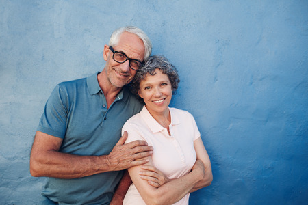 Portrait of smiling mature couple standing together against blue background. Happy middle aged man and woman against a wall.の写真素材