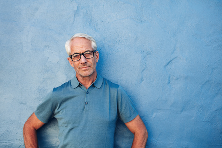 Photo for Portrait of a mature man standing against a blue background with copy space. Caucasian man wearing glasses leaning to a wall and staring at camera. - Royalty Free Image