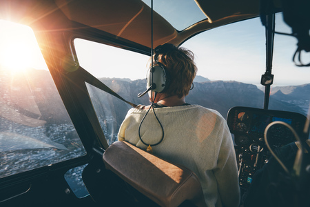 Rear view of female tourist on helicopter looking out of the window. Helicopter passenger admiring the view.