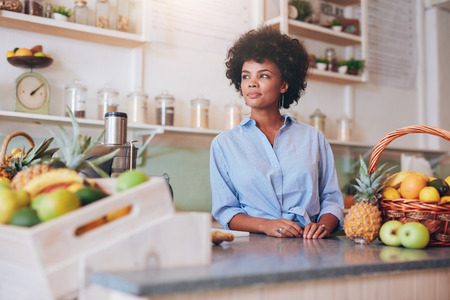 Foto de Portrait of a confident young female employee standing at the juice bar counter. African woman working at juice bar and looking away. - Imagen libre de derechos
