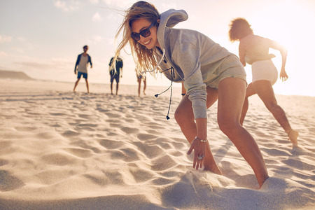 Young woman running race on the beach with friends. Group of young people playing games on sandy beach on a summer day.