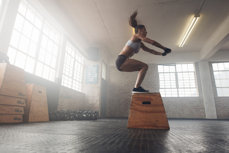 Photo for Side view image of fit young woman doing a box jump exercise. Muscular woman doing a box squat at the cross fit gym - Royalty Free Image
