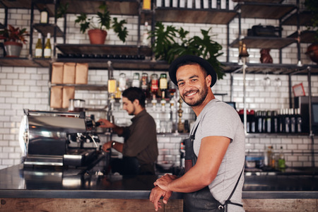 Photo pour Portrait of happy young male coffee shop owner standing with barista working behind the counter making drinks. - image libre de droit