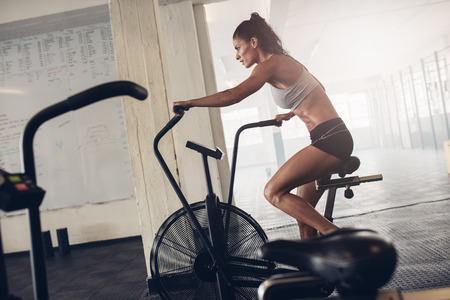 Foto de Fit young woman using exercise bike at the gym. Fitness female using air bike for cardio workout at crossfit gym. - Imagen libre de derechos