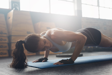 Photo for Shot of young woman doing push-ups at the gym. Strong female athlete doing pushups on exercise mat at gym. Female exercising on fitness mat at gym. - Royalty Free Image