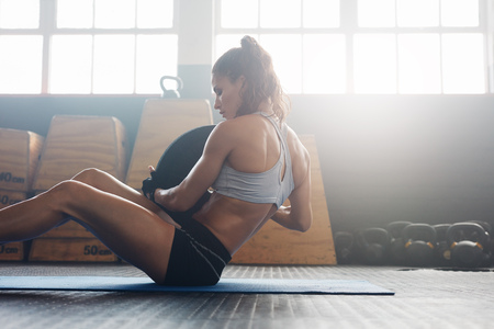 Foto de Woman doing sit ups with holding a weight plate. Fitness woman working out on core muscles at cross fit gym. - Imagen libre de derechos