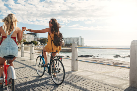 Rear view shot of two young woman holding hands and riding bicycles on a seaside promenade.