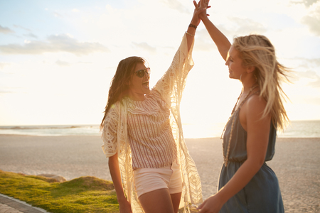Photo pour Two young women on the beach giving high five. Women friends enjoying beach vacation. - image libre de droit
