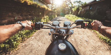 Rider driving motorcycle on a rural road. Point of view shot with focus motorbike handlebar and man hands.
