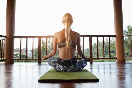 Rear view shot of young woman practicing yoga while sitting in lotus position on exercise mat. Sporty woman padmasana pose from the back.
