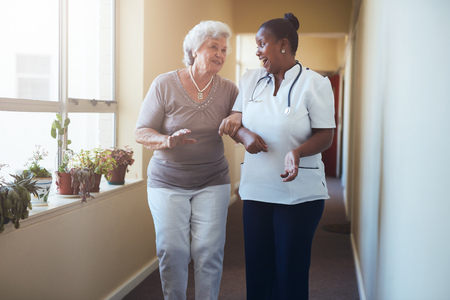 Foto de Portrait of happy healthcare worker walking and talking with senior woman. Elder woman gets help from nurse for a walk through nursing home. - Imagen libre de derechos