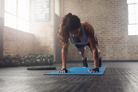 Photo for Young muscular woman doing core exercise on fitness mat in the gym. Fit female doing press-ups during the training in the health club. - Royalty Free Image