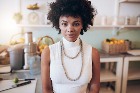 Closeup portrait of young african woman standing at juice bar. Attractive female looking at camera.