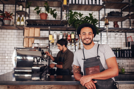 Foto de Portrait of male coffee shop owner standing at the counter with barista working in background making drinks. - Imagen libre de derechos