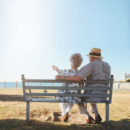 Rear view of senior couple relaxing on a bench with woman pointing out to sea. Retired man and woman sitting on a bench outdoors and enjoying the view.