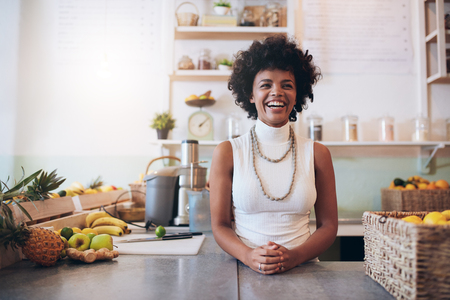 Photo pour Portrait of young african woman standing behind juice bar counter looking at camera and smiling. Happy juice bar owner. - image libre de droit