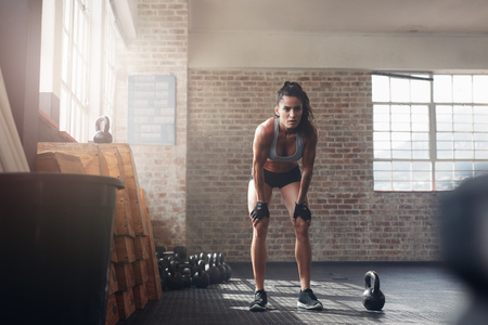 Photo pour Full length shot of confident young woman at crossfit gym. Muscular sportswoman standing with her hands on knees looking focused about her fitness workout. - image libre de droit